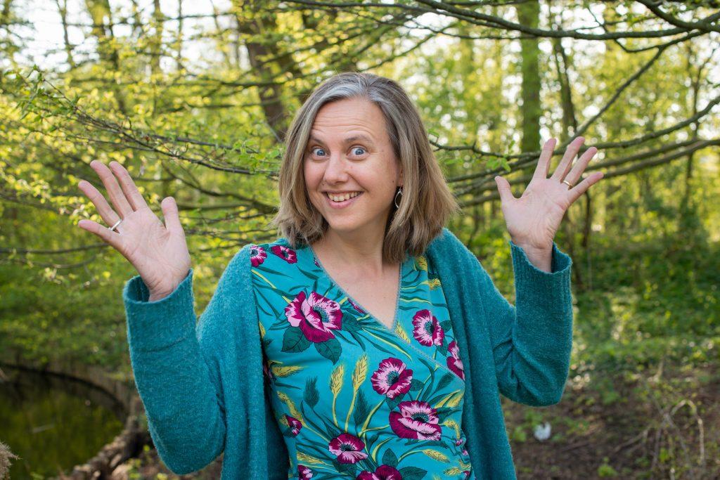 Dit is Paulien Bruijn met een grote glimlach op haar gezicht. Ze heeft haar handen in de lucht en maakt het gebaar voor applaus.